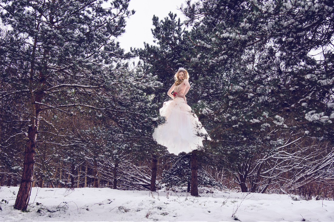 Winter wedding Brides levitating in the snow at Nutfield Priory