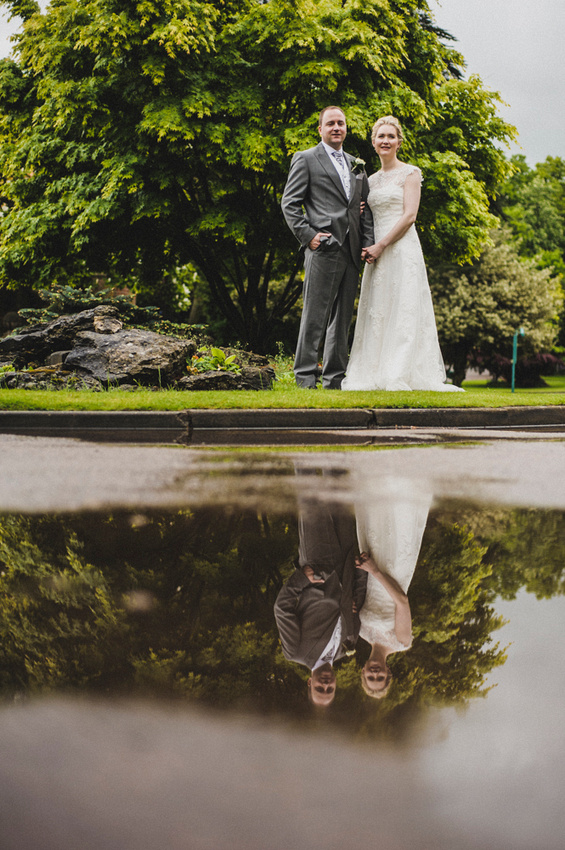 Wedding couple reflected in puddle at The Warren, Bromley