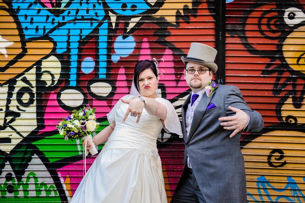 Alternative wedding photography, bride and groom with graffiti