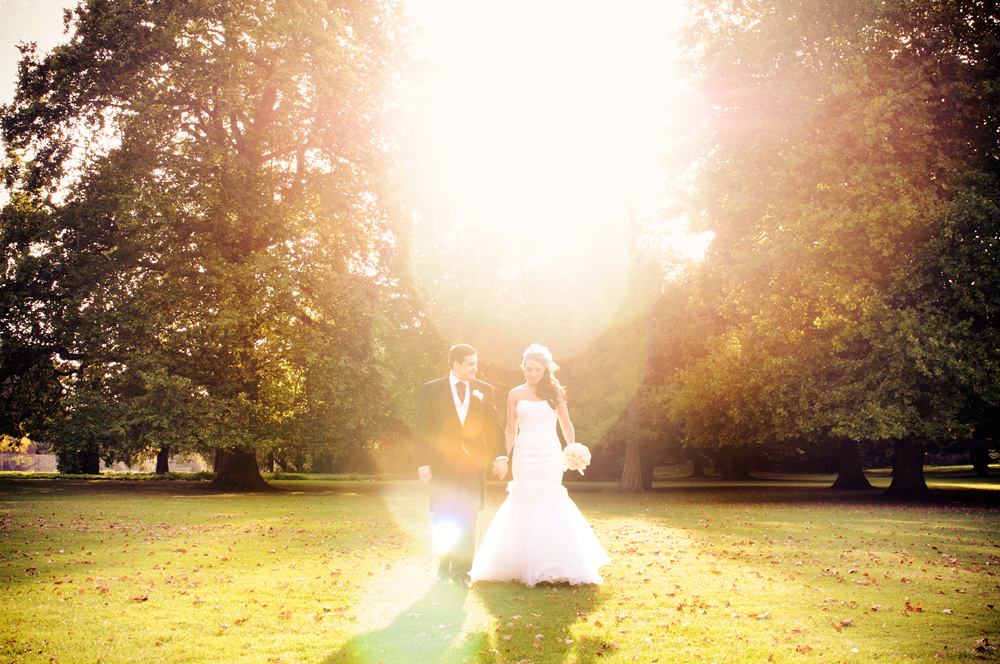 Bride and groom walking at Bradbourne House, photo with flare