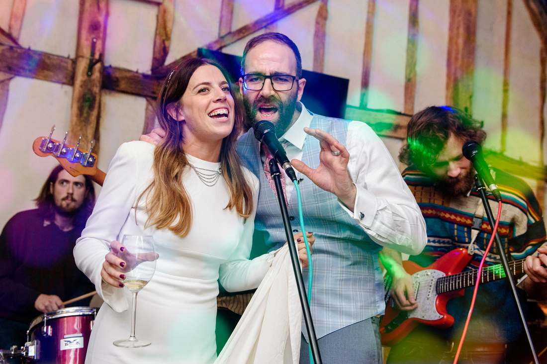 Bride and groom singing with the band on their wedding day at Alpheton Hall Barns