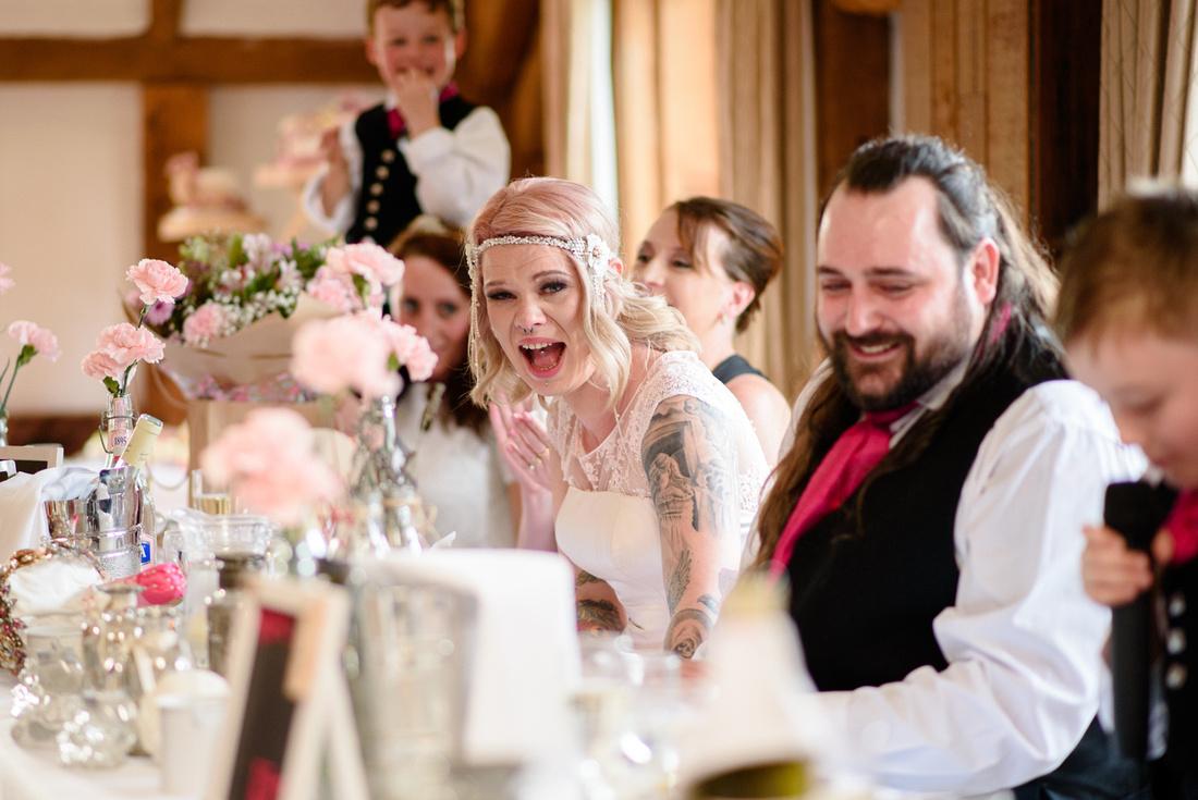 Bride laughing duringl best mans speech at High Rocks Tunbridge wells