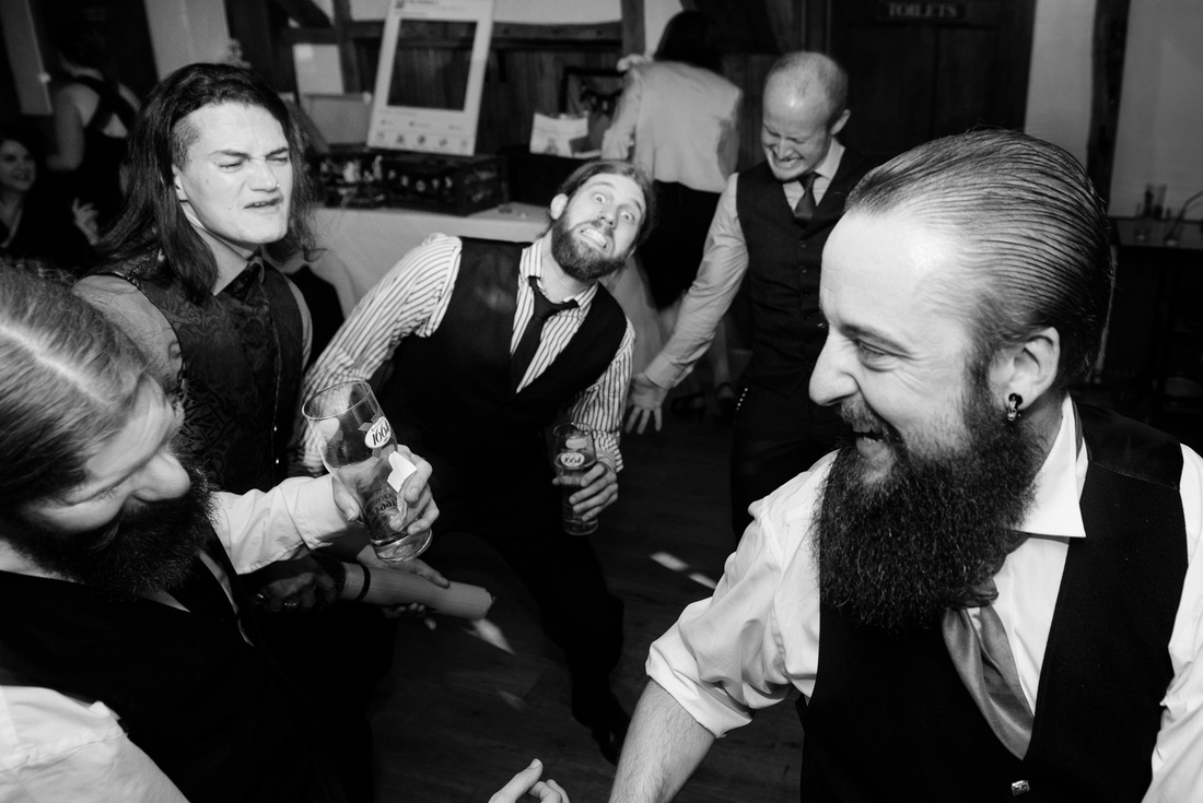 Black and white photo of wedding guests rocking out and partying hard