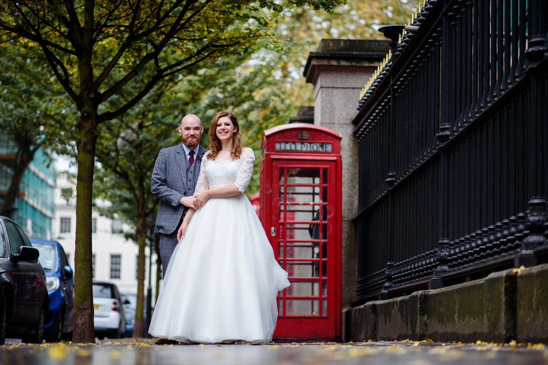 Bride and groom standing out side red phone box  in a London street on their wedding day