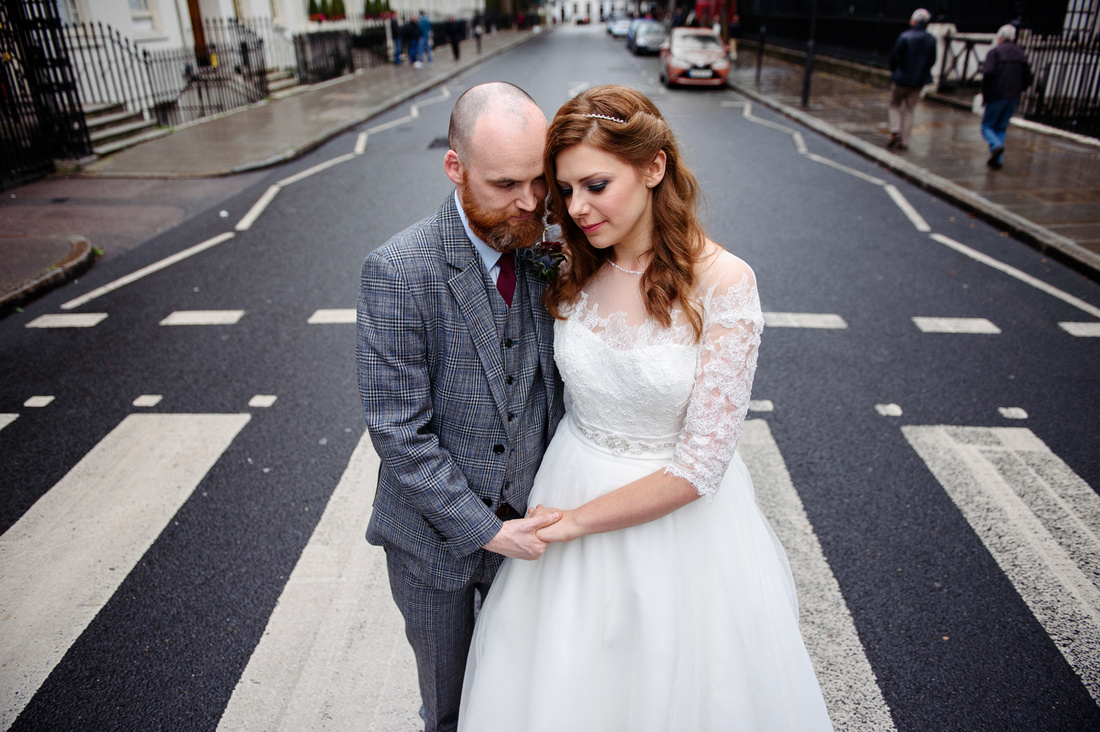 Bride and groom standing on zebra crossing in London street on their wedding day