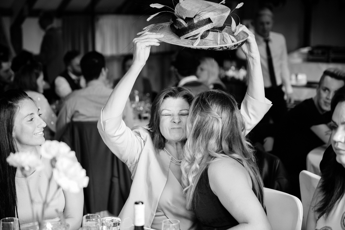 Brides mum lifting her large hat to kiss another wedding guest