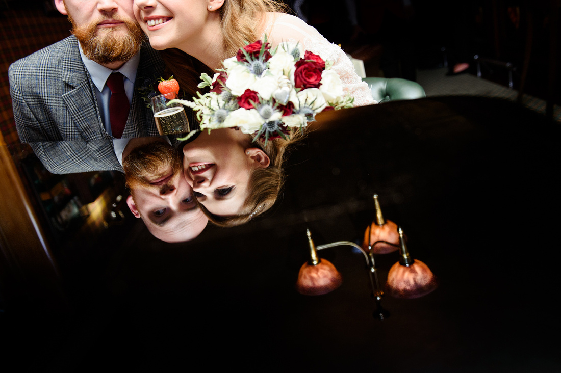 Reflection of the bride and grooms face in the grand piano at The Montague on the Gardens on their wedding day