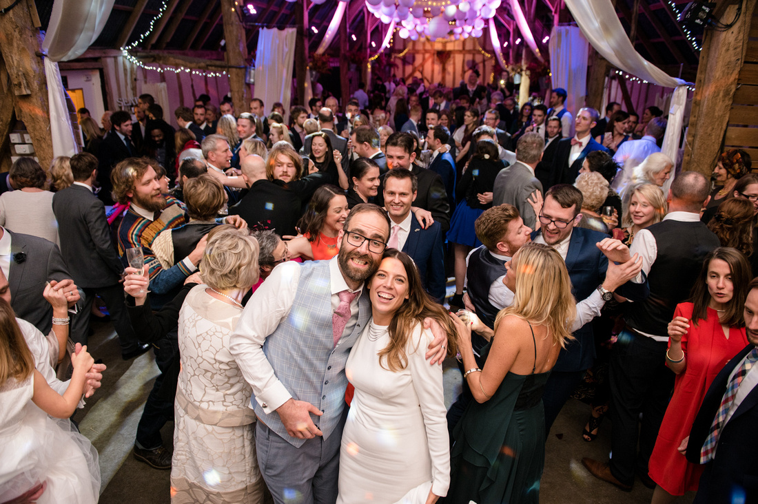 Bride and groom surrounded by all their guests dancing at Alpheton hall barns