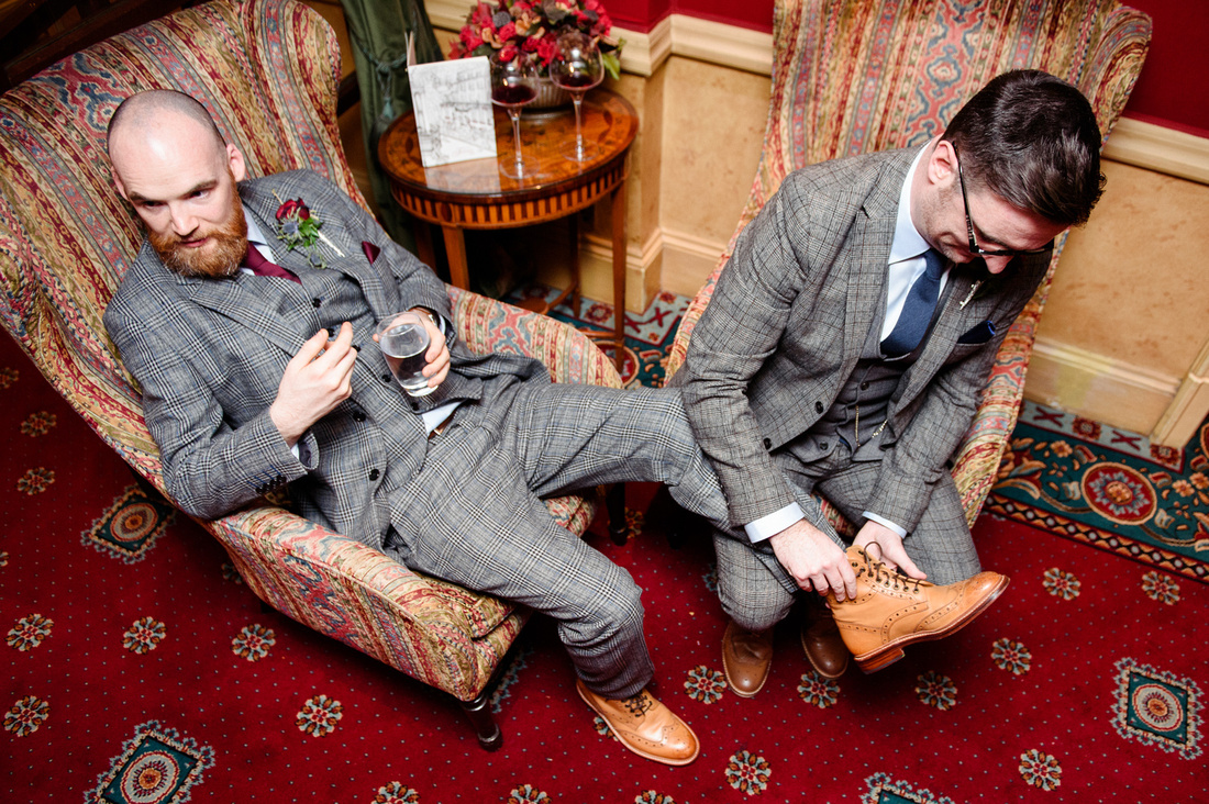 Best man helps the groom tie his shoes at The Montague on the Gardens