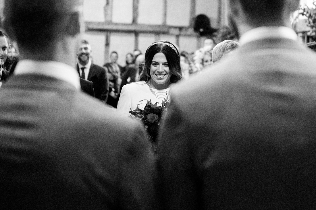 Bride walking down the aisle at before her wedding ceremony at  Alpheton Hall barns