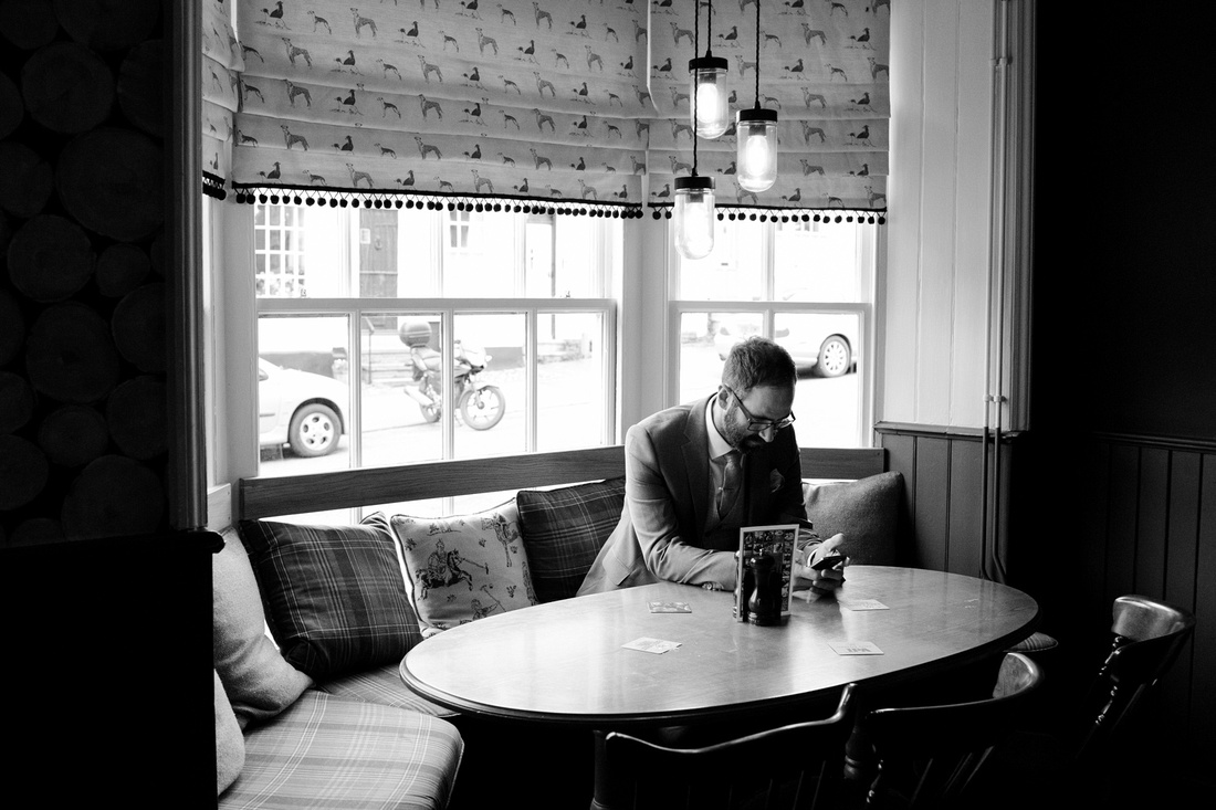 Black and white photo of the groom sitting alone before his wedding, lavenham, suffolk