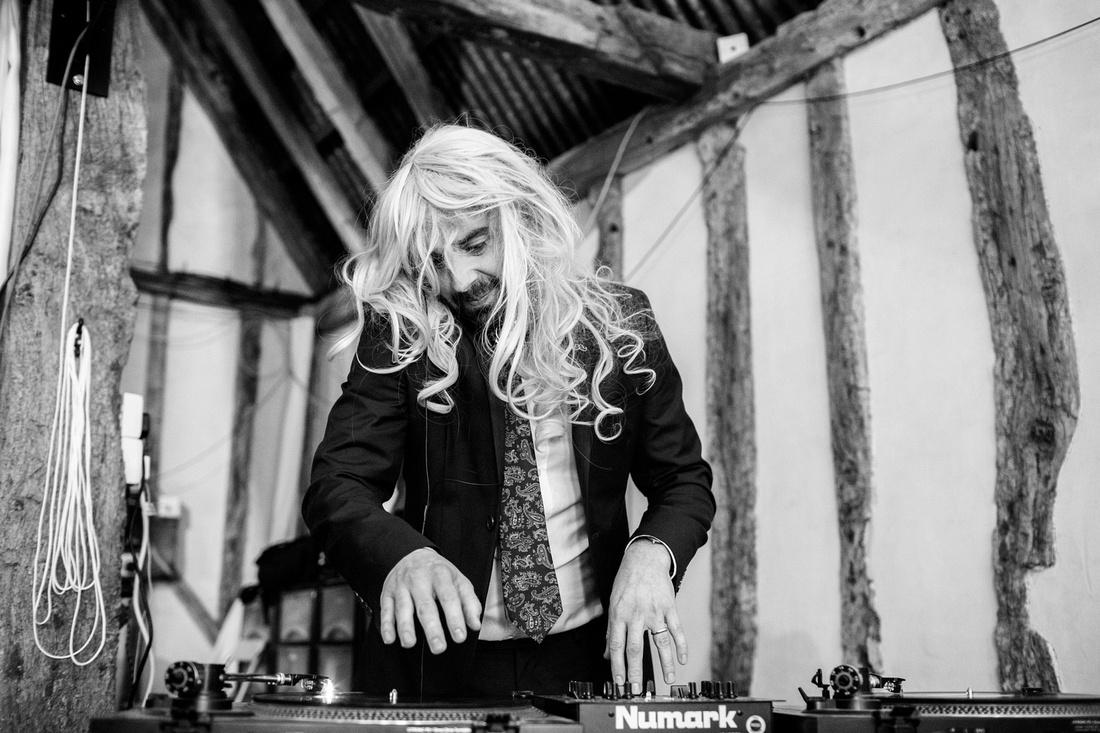 Vinyl DJ in fancy dress wig at a wedding at  Alpheton Hall Barns