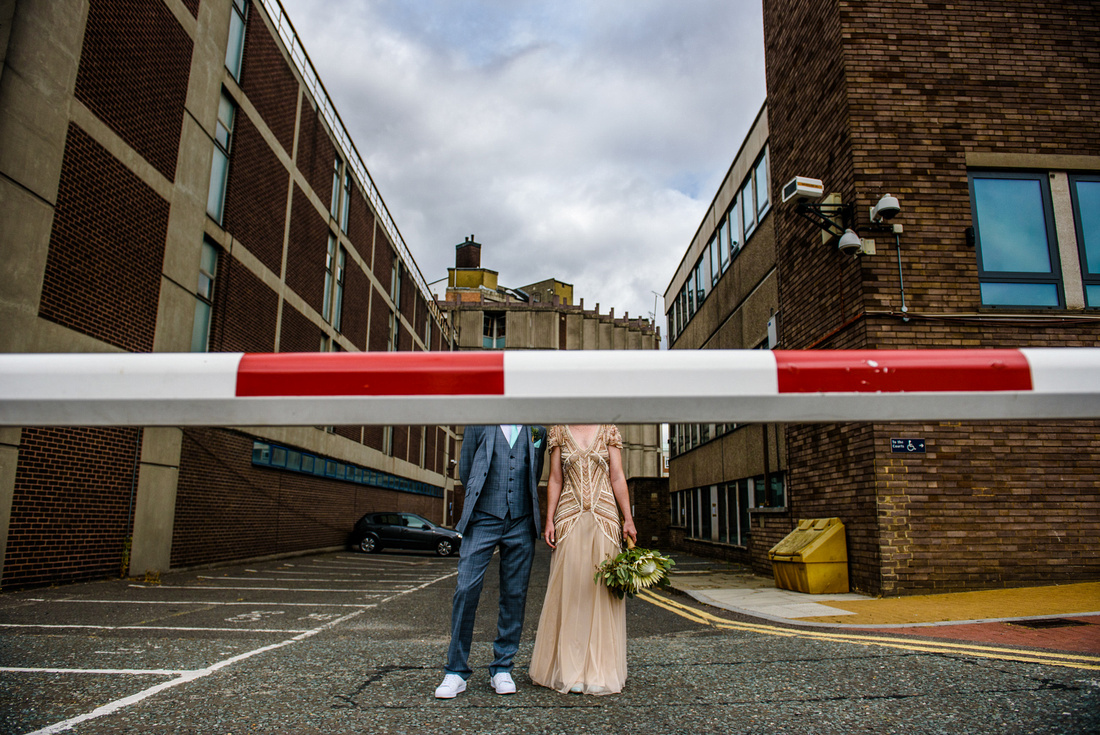 Quirky street portrait of bride and groom on their wedding day